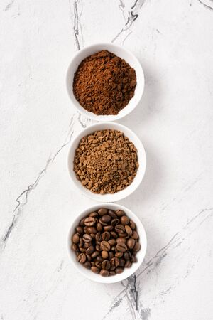 Top view of roasted beans with ground coffee in white bowl on marble background Imagens