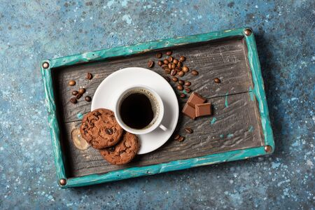 Top view of tasty chocolate chip cookies and coffee on wooden tray and blue concrete background