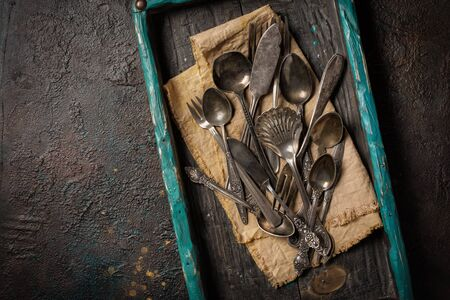 Top view of vintage silver cutlery or silverware on dark concrete background with copy space