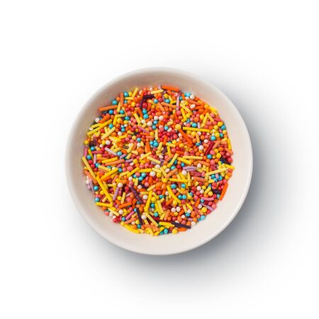 Top view of multicolored sugar sprinkles or confetti in bowl isolated on white background