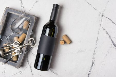 Top view of lying red wine bottle with empty label, corkscrew and glass for tasting on white marble background with copy space