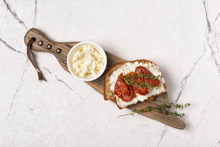 Top view of tasty sandwich with healthy bread, soft cheese and sun-dried tomatoes on rustic wooden board and white marble background Reklamní fotografie