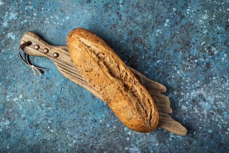 Top view of whole loaf of fresh wholegrain bread on wooden cutting board on blue concrete background