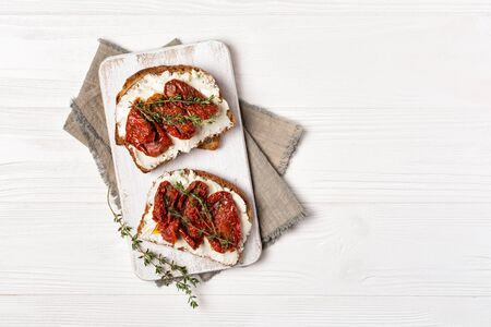 Top view of tasty sandwiches with healthy bread, soft cheese and sun-dried tomatoes on white wooden background with copy space Reklamní fotografie