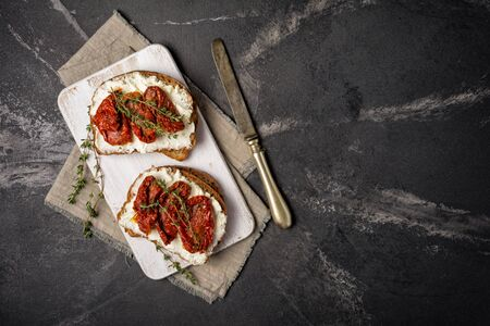 Top view of tasty sandwiches with healthy bread, soft cheese and sun-dried tomatoes on black marble background with copy space