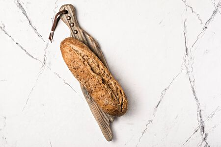 Top view of whole loaf of fresh wholegrain bread on wooden cutting board on white marble background with copy space