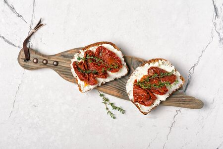 Top view of tasty sandwiches with healthy bread, soft cheese and sun-dried tomatoes on white marble background