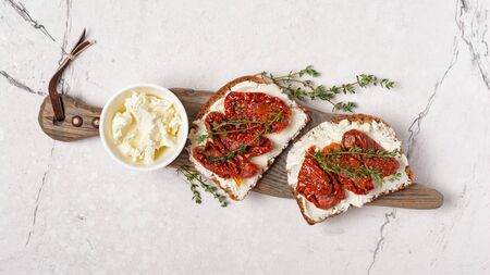 Top view of tasty sandwiches with healthy bread, soft cheese and sun-dried tomatoes on rustic wooden board and white marble background