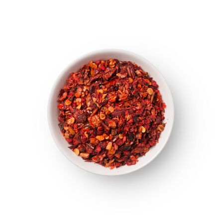 Top view of dried hot red pepper flakes in bowl for spicy food isolated on white background