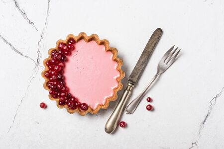 Top view of tasty berry dessert with vintage silver cutlery on white marble background