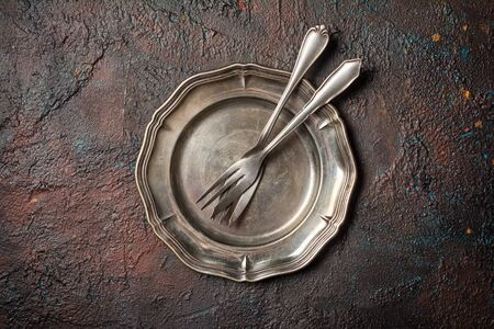 Top view of vintage silver cutlery or silverware on dark concrete background