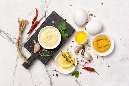 Top view of ingredients for mayo sauce as mustard, eggs, spices on white marble background Stockfoto