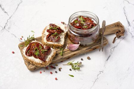 Sandwich with bread, soft cheese and homemade sun-dried tomatoes with green herbs, garlic and spices in olive oil on white marble background