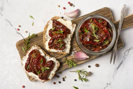 Top view of sandwich with bread, soft cheese and homemade sun-dried tomatoes with green herbs, garlic and spices in olive oil on white marble background Reklamní fotografie