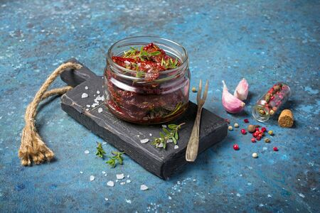Homemade sun-dried tomatoes with green herbs and spices in olive oil on black wooden board and blue concrete background