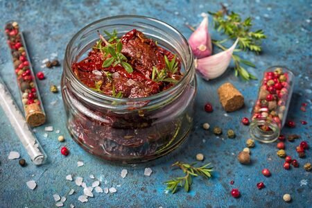 Close-up of homemade sun-dried tomatoes with green herbs, garlic and spices in olive oil on blue concrete background