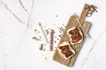 Top view of sandwich with soft cheese and homemade sun-dried tomatoes with herbs, garlic, spices in glass test tube on wooden board and white marble background with copy space Reklamní fotografie - 150529675