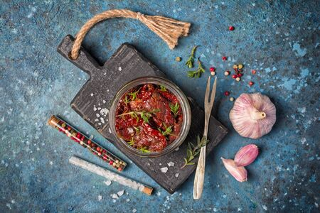 Top view of homemade sun-dried tomatoes with green herbs, garlic and spices in olive oil on black wooden board and blue concrete background Reklamní fotografie