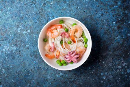 Top view of bowl with chinese rice noodles, tasty shrimps, bebe octopus and green peas on blue concrete background Archivio Fotografico