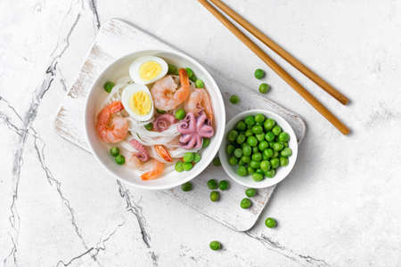 Top view of bowl with chinese rice noodles, tasty shrimps, bebe octopus, chicken eggs and green peas on white marble background Archivio Fotografico