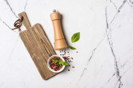 Top view of bright mix peppercorns in bowl with wooden pepper mill and green basil leaves for aromatic food on white marble background with copy space