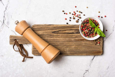 Top view of bright mix peppercorns in bowl with wooden pepper mill and green basil leaves for aromatic food on white marble background Standard-Bild