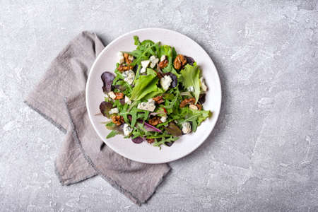 Top view of healthy and tasty vegetarian food. Salad with mix of fresh green leaves, blue cheese and walnuts on grey concrete background