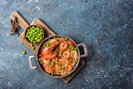 Top view of frying pan with chinese rice noodles, tasty prawns, green peas in bowl and red pepper on wooden board and blue concrete background