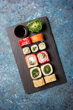Top view of traditional japanese food the bright tasty sushi rolls with salmon, caviar, avocado, cream cheese and soy sauce in black bowl on blue concrete background