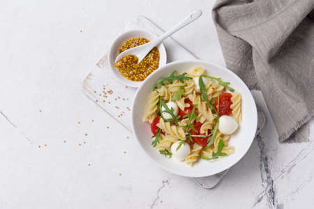Top view of tasty vegetarian pasta with cherry tomatoes, soft cheese mozzarella, mustard sauce and green arugula leaves on white marble background