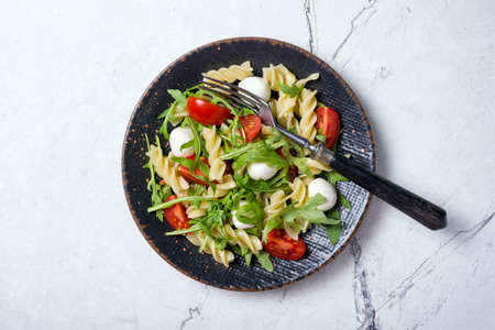 Top view of tasty vegetarian pasta with cherry tomatoes, soft cheese mozzarella and green arugula leaves on white marble background 版權商用圖片