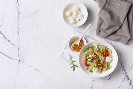 Top view of tasty vegetarian pasta with cherry tomatoes, soft cheese mozzarella, mustard sauce and green arugula leaves on white marble background with copy space