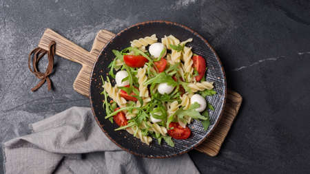 Top view of tasty vegetarian pasta with cherry tomatoes, soft cheese mozzarella and green arugula leaves on dark concrete background