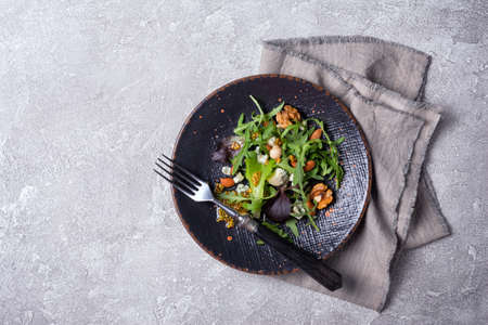 Top view of healthy and tasty vegetarian food. Salad with mix of fresh green leaves, blue cheese, nuts and mustard sauce on grey concrete background