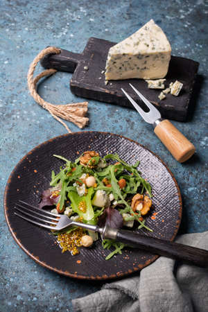 Healthy and tasty vegetarian food. Salad with mix of fresh green leaves, blue cheese, nuts and mustard sauce on blue concrete background