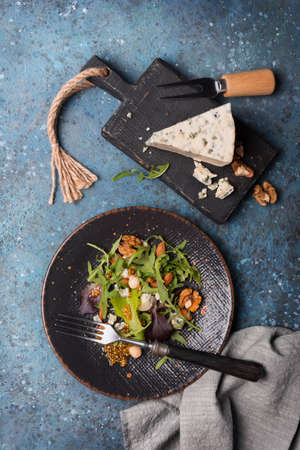 Top view of healthy and tasty vegetarian food. Salad with mix of fresh green leaves, blue cheese, nuts and mustard sauce on blue concrete background