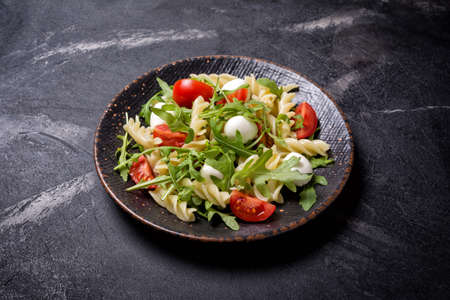 Tasty vegetarian pasta with cherry tomatoes, soft cheese mozzarella and green arugula leaves on black marble background 版權商用圖片