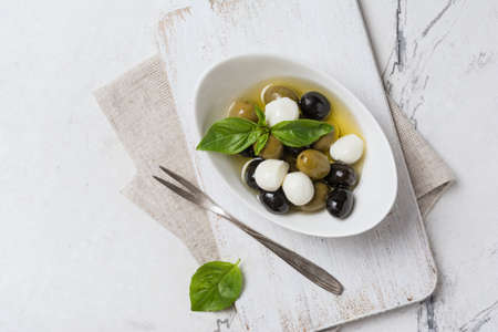 Top view of tasty mix green and black olives with mozzarella, basil leaves on white wooden board and marble background