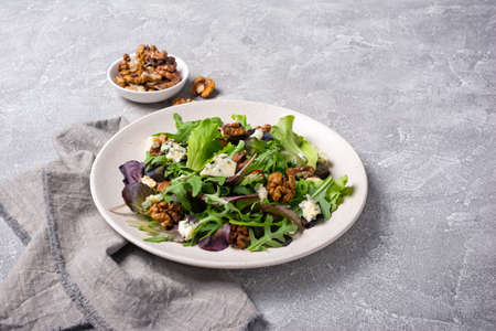 Healthy and tasty vegetarian food. Salad with mix of fresh green leaves, blue cheese and walnuts on grey concrete background