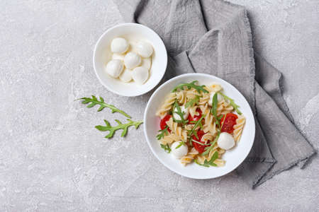 Top view of tasty vegetarian pasta with cherry tomatoes, soft cheese mozzarella and green arugula leaves on grey concrete background