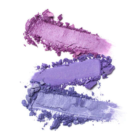 Flat lay of brush strokes. Broken shiny bright purple eyeshadow as samples of cosmetic beauty products isolated on white background