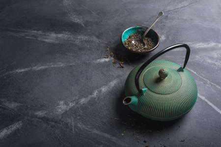 Traditional green or turquoise asian cast iron kettle and dry tea leaves on black marble background with copy space