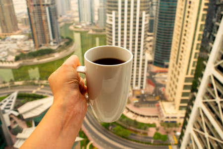 Female hand holds big white cup of morning coffee with city skyscrapers view of modern city Dubai. Coffee cup on city background.