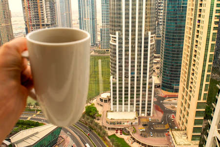 Female hand holds big white cup of morning hot drink - coffee or tea with city skyscrapers view of modern city Dubai with copy space. Coffee cup on city background with copy space.