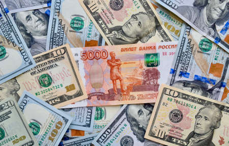Russian national currency on top of US dollar banknote, top view of mixed rouble banknotes. Russian and American paper money. Rubles and US dollars exchange rate.