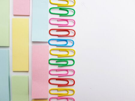 Multicolored blue, red yellow, pink, green, white metal paper clips on a white background.