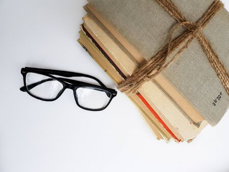 A stack of old books tied with jute rope. Black glasses on a white background with a shadow. High quality photo