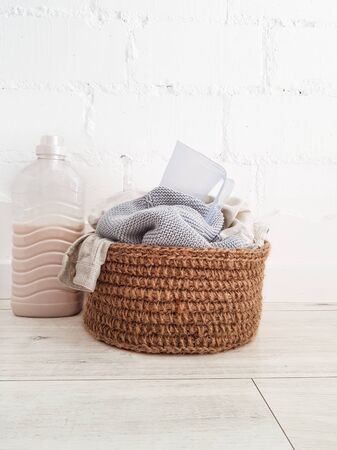 Jute brown basket with beige and white linen. A plastic bottle of liquid and a clear blue glass against a white brick wall. High quality photo