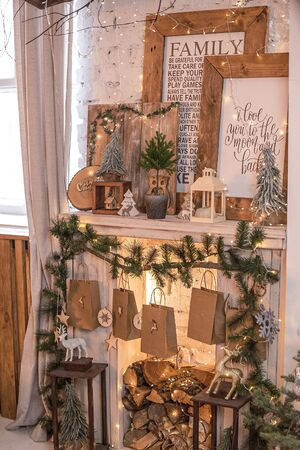 Merry Christmas. New years interior with a fireplace, Christmas lights, paintings, deer and firewood. High quality photo. Stock Photo