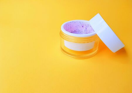Transparent jar with cream and white lid on a bright yellow background. Space for text. High quality photo